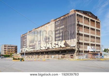 Port of Piraeus Greece - Mai 30 2017: One of the old Silo and dry docks buildings with the wall painting near Silos Ietioneias Coast with its Floating Museum