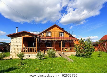 Wooden cottage with terrace and white brick side construction