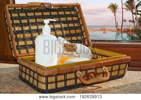 Case with bath implements: soap soap dispenser shampoo and towel in front of the window. Through the window - look at the pool and sea