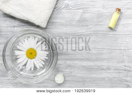 hands care set for manicure with chamomile on gray wooden background top view space for text.
