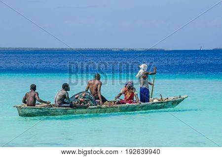 Zanzibar Tanzania - November 6 2016: Five fishermen paddling a wooden boat through the Indian ocean near the coastline of Zanzibar.