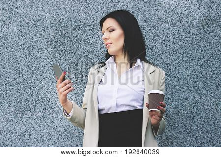Keep In Touch. Portrait Of Confident Business Woman In Smart Casual Wear Looking At Her Phone And Ke