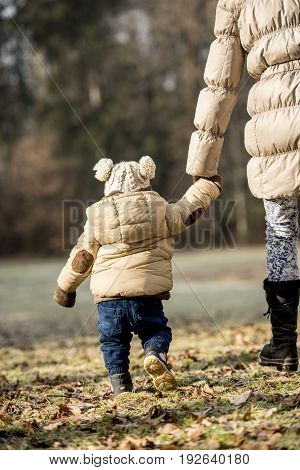 Rear view of a mother holding hands with her toddler child outside in forest both wearing winter jackets.