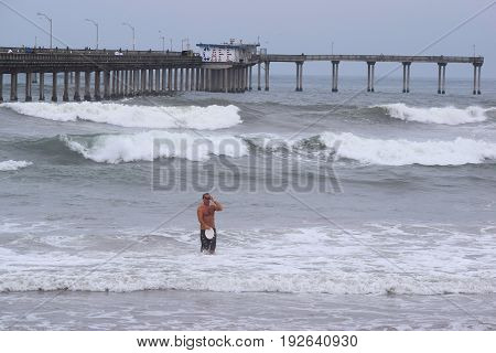 June 22, 2017 in Ocean Beach, CA:  Waves crashing onshore including a man in the water with a large concrete pier beyond with a café taken in Ocean Beach, CA where people can enjoy the beach and pier