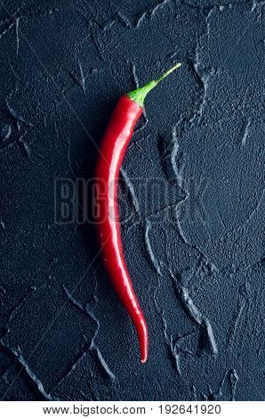 One red hot chili pepper over dark concrete background. Overhead view of chilli peppers on black stone table. Minimalism style. Top view.