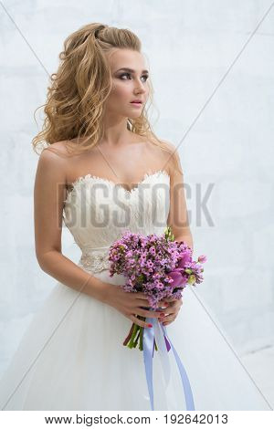 Gorgeous young bride in an exquisite dress posing with a violet bouquet in studio