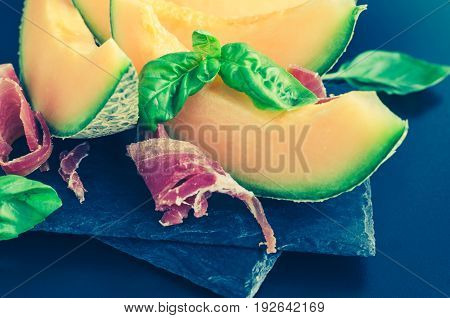 Concept of italian food with melon and prosciutto on dark background. Traditional appetizer antipasto. Selective focus.