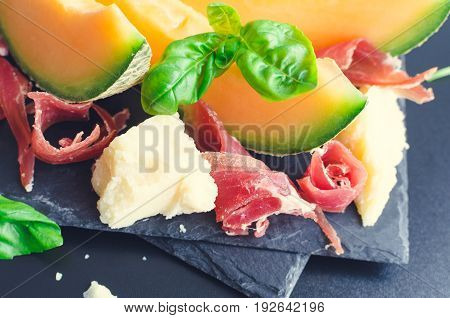 Concept of italian food with melon prosciutto and Parmesan cheese on dark background. Traditional appetizer antipasto. Selective focus.