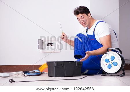 Funny young electrician working on socket at home