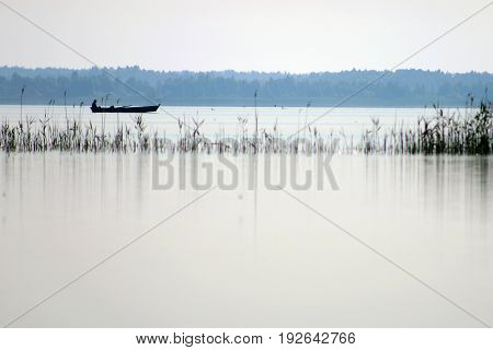 Fisherman sitting on boat silhouette. Catch fish in the lake