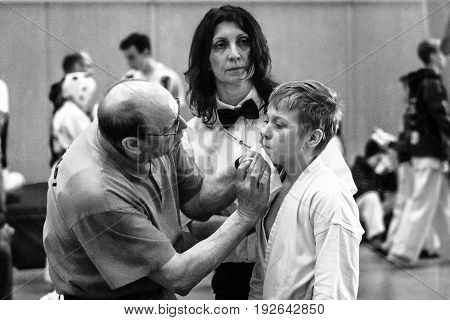 BERLIN - MARCH 18 2017: Fighter on the tatami. First aid to a fighter. Black and white. European championship Kyokushin World Union (KWU) for Children and Youth.