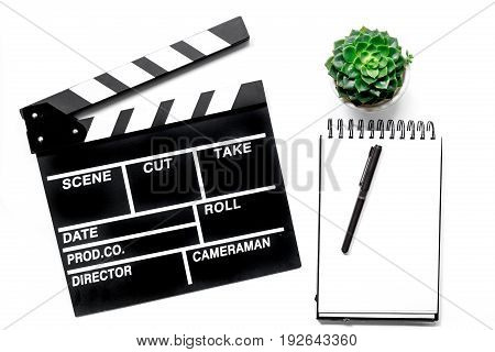 Work table of producer. Movie clapperboard and notebook on white background top view.