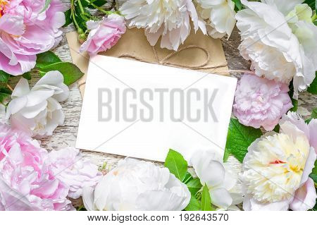 blank greeting card and envelope in frame of pink and white peonies and roses over rustic wooden background. flat lay. top view with copy space. wedding invitation