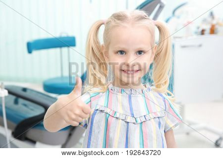 Cute little girl showing thumb up sign at dentist's office