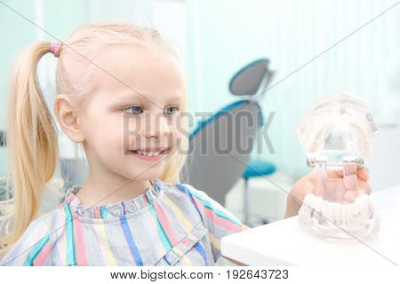 Cute little girl with plastic jaw mockup at dentist's office
