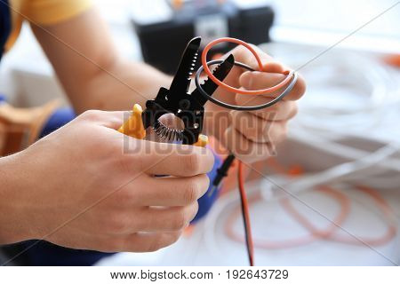 Electrician cutting wires indoors, closeup