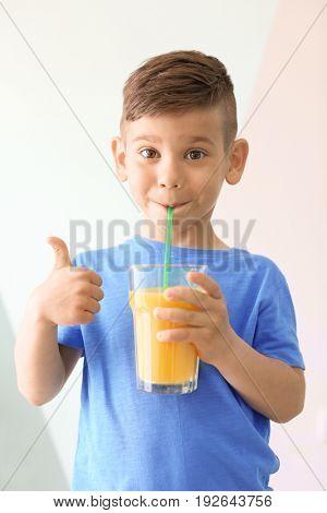 Cute little boy drinking juice on light background