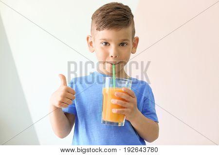 Cute little boy drinking juice on light color background