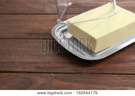 Dish with butter on wooden table
