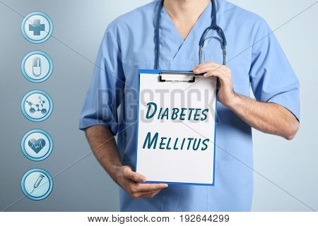 Health care concept. Doctor holding clipboard with text DIABETES MELLITUS on color background