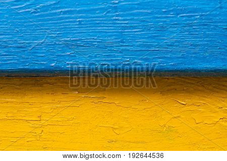 An old bench in the street. The combination of colors is similar to the flag of the state of Ukraine. Color image blue yellow. Horizontal frame