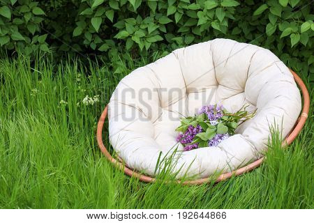 Beautiful lilac flowers on lounge chair in garden