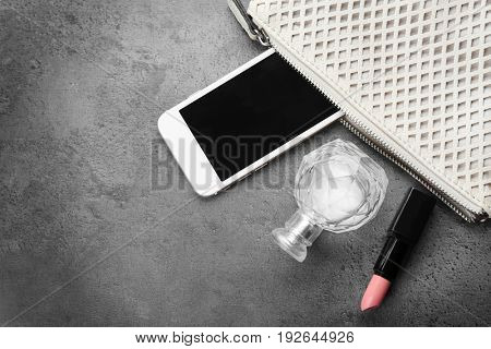 Cosmetics, perfume and phone near small bag on grey background