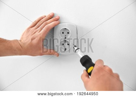 Electrician repairing socket, closeup