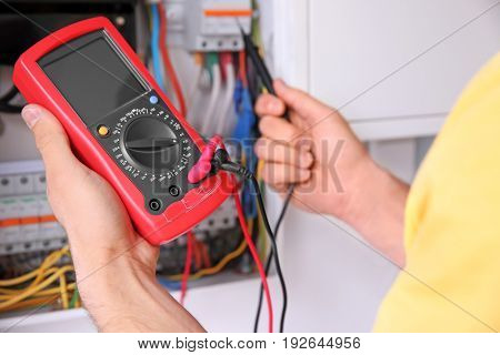 Electrician measuring voltage in distribution board, closeup