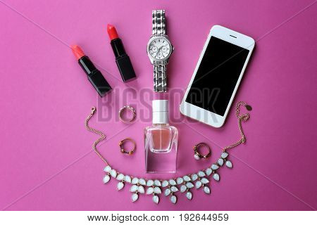 Perfume, accessories, cosmetics and phone on color background