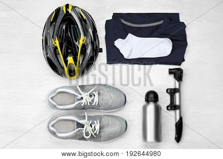 Bicycle accessories and biking clothes on white wooden background