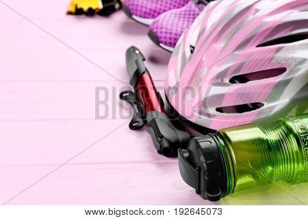 Set of bicycle accessories on color wooden background