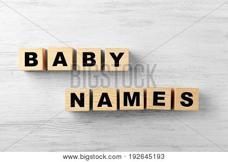 Cubes with words BABY NAMES on wooden background