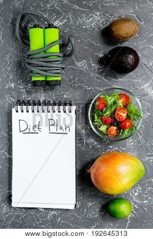 Slimming. Notebook for diet plan, fruits and salad and skipping rope on grey stone table top view mock up.