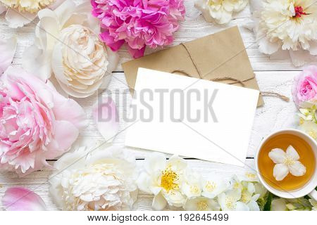 blank greeting card or wedding invitation with tender peonies and roses flowers with cup of green jasmine tea. mock up. flat lay. top view