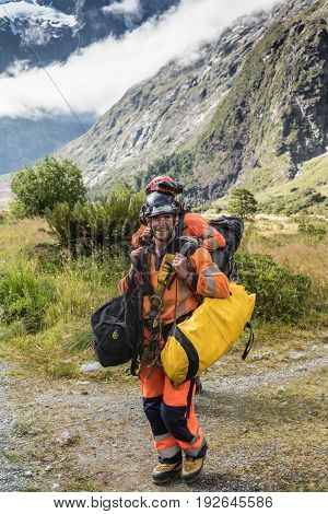 Fiordland National Park New Zealand - March 16 2017: Two air-dropped government park researchers trekking through the wilderness in full gear with bags of equipment. Tall mountains backdrop. Green vegetation.