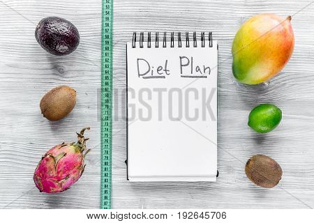 Tasty food for slimming. Notebook for diet plan and fruits on grey wooden table top view mock up.