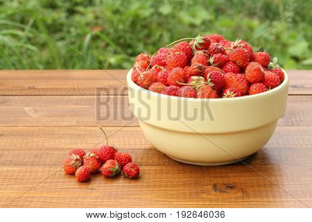 Ripe red pine strawberry in yellow bowl on brown wooden table against green grass background