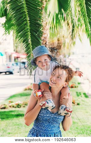 Happy family at summer time on the background of palm tree leaf in Zadar Croatia. Mother and son have fun. Family Lifestyles concept. Beautiful young woman and her child in vacation