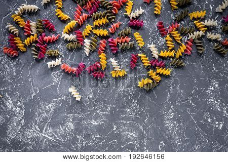 Fusilli pasta on grey stone table top view copyspace.