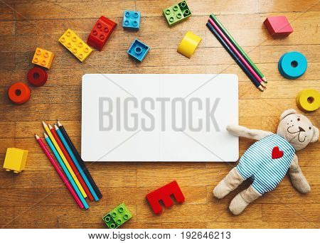 Child or baby play set with empty book or notepad toy wooden blocks plastic constructor colored pencils teddy bear. Back to school education concept. Kindergarten or preschool background.