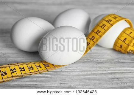 Eggs with measuring tape on wooden table