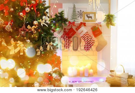 Christmas decoration of fireplace and fir tree in living room. Festive and blurred lights design. Celebration of new year 2018