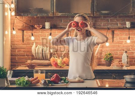 Young female cooking healthy fresh meal in the kitchen and having fun.