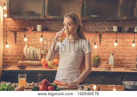 Young female cooking healthy fresh meal in the kitchen drinking juice