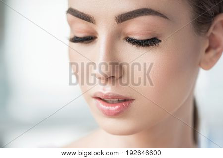 Natural make-up. Close up of face of pensive young woman having perfect make-up on her skin and lips, eyes and brows. Her eyes half closed