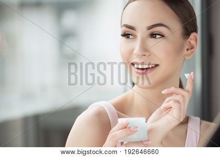 Jolly young woman is holding piece of cream on point finger and jar with face cream in hand. She is applying cream on cheeks with toothy smile. Copy space in left side