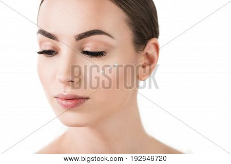 Close up of face of calm young girl with three dots of cream on her cheek. She is looking down and her eyes half closed. Isolated