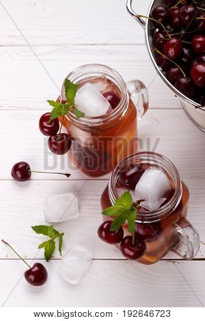 Detox fruit infused flavored water with cherry, lemon and mint on white background. Refreshing summer homemade cocktail