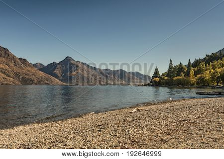 Queenstown New Zealand - March 15 2017: Looking west from downtown shore shows dry desolate brown mountains across the deep blue Wakatipu Lake small green forest and pebble beach. Blue sky.